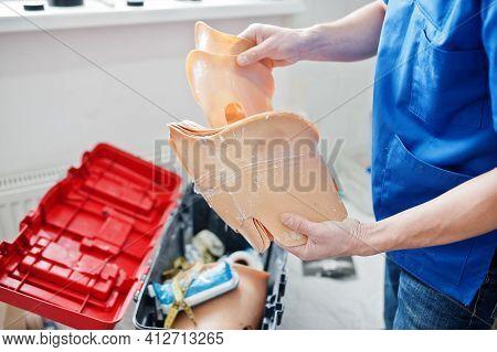 Prosthetist Man Making Prosthetic Leg While Working In Laboratory.
