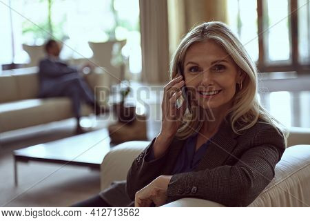 Charming Woman Talking On Her Phone In A Hotel Waiting Area
