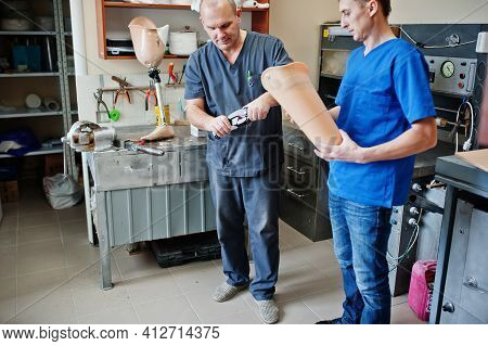 Two Prosthetist Man Workers Making Prosthetic Leg While Working In Laboratory.