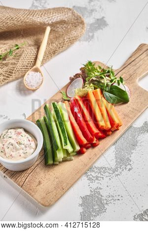 Fresh vegetable food platter on white table. Slices vegetable on wooden board with dip sauce. Rustic food concept