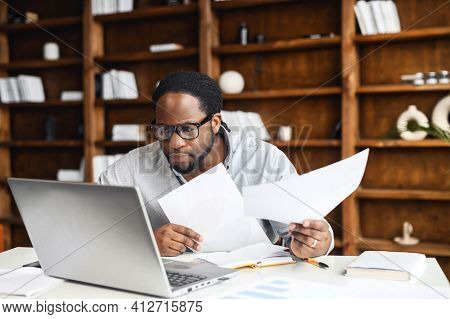 Young Concentrated Manager Sitting In Cabinet Surrounded With Papers Documents, Accountant Analyst H