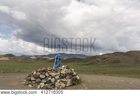 Ovoo With Blue And Orange Flags In Mongolia, A Sacred Place In Buddhism On A Mountain In Mongolia.