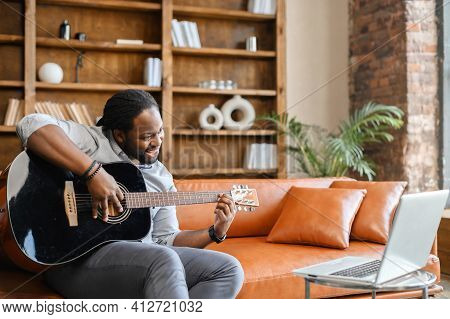 African Man Sitting On The Leather Sofa With Guitar In A Creative Space Or At Home, Playing A Song F