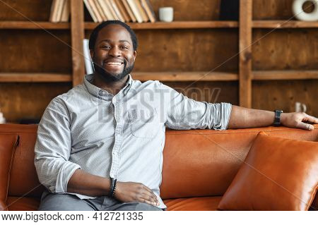 Ethnic Black Unshaved Plump Man With Dreadlocks Sitting On The Leather Sofa And Smiling, In A Normal