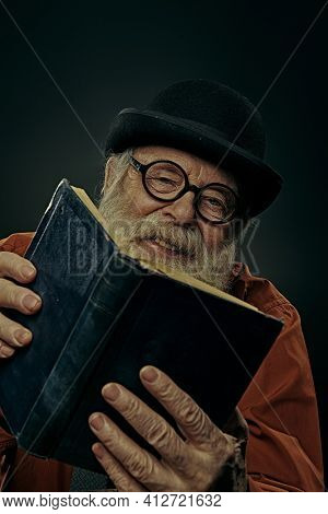 A wise old man with a long gray beard in a bowler hat and glasses is reading an old book and laughing. Black background.