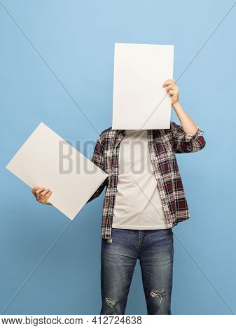 Portrait Of Young Man With Blank Sheets Of Paper On Blue Background.