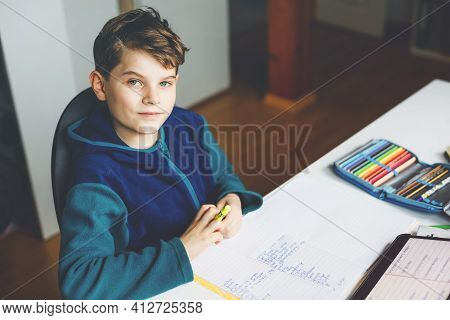School Kid Boy Learning At Home With Tablet For School. Adorable Child Making Homework And Using Pad