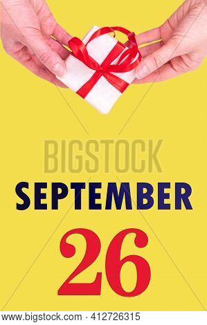 September 26th. Festive Vertical Calendar With Hands Holding White Gift Box With Red Ribbon And Cale