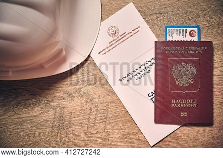 White Hardhat, Russian Foreign Passport And Turkish Work Permit At Wooden Desk Top Down View. Concep