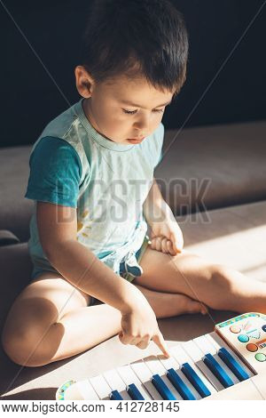 Caucasian Boy Is Playing The Piano On The Floor Discovering New Hobby