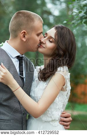 Valentine's Day, A Couple In Love Hugging And Kissing In The Park. Man Hugs Beautiful Woman, Engagem