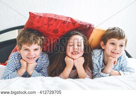 Three Happy Kids In Pajamas Celebrating Pajama Party. Preschool And School Boys And Girl Having Fun