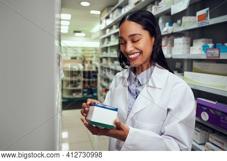 Portrait Of Cheerful Woman Wearing Labcoat Reading Instructions On Medicine Box Standing In Chemist