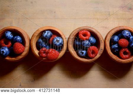 Raspberries and blueberries in wooden bowls.