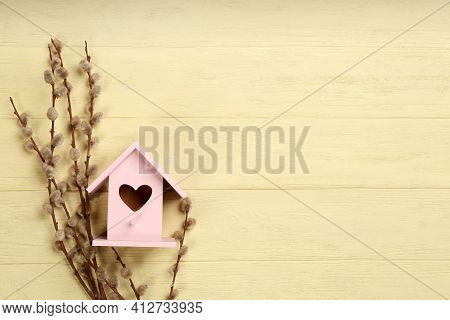 Beautiful Bird House With Heart Shaped Hole And Willow Branches On Pale Yellow Wooden Background, Sp