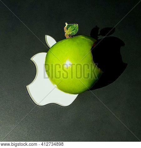 An Unripe Apple Lies On The Background Of A Famous Brand