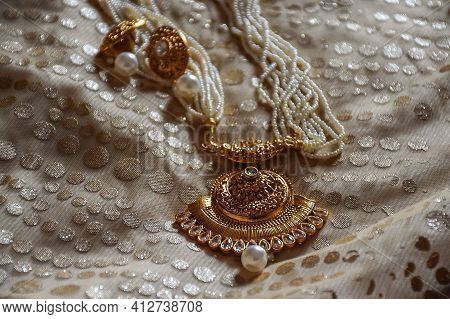 Stock Photo Photo Of A Beautiful White Pearl Necklace With Golden Pendent And Earrings On White Back