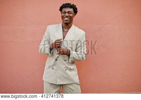 Stylish Afro Man In Beige Old School Suit Against Pink Wall. Fashionable Young African Male In Casua