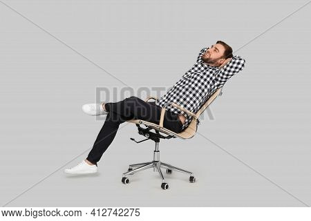 Young Man Relaxing In Comfortable Office Chair On Grey Background