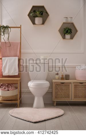 Stylish Bathroom Interior With Toilet Bowl And Other Essentials