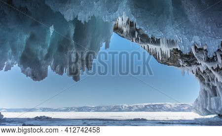 Ice-covered Stone Grotto. Bizarre Ice Stalactites Hang From The Ceiling Against The Azure Sky. Ahead