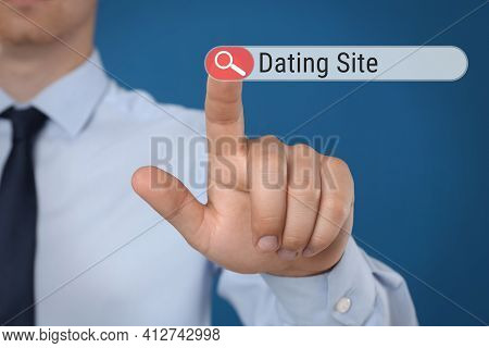 Man Pointing At Search Bar With Request Dating Site On Blue Background, Closeup
