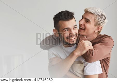 Candid Waist Up Portrait Of Carefree Gay Couple Embracing Indoors And Laughing Happily While Posing