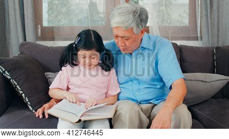 Asian Grandfather Relax At Home. Senior Chinese, Grandpa Happy Relax With Young Granddaughter Girl E