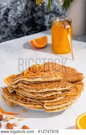 Crepes Or Blinis Stacked On A Plate With Nuts And Orange Jam. Spring Breakfast.
