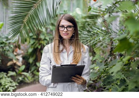 Greenhouse And Tropic Plants. Young Attractive Caucasian Woman Scientist, Posing To Camera, While In