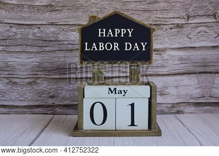 Text On Chalkboard And White Cube Block On Wooden Table - Happy Labour Day
