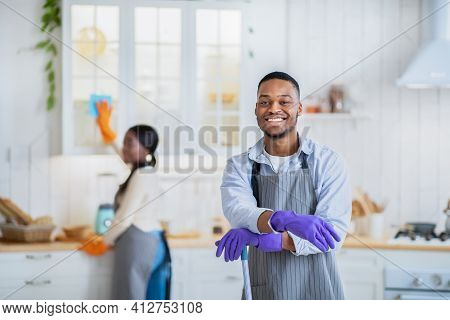 Portrait Of Positive African American Guy With Mop Ready For Cleanup, His Wife Washing Kitchen Cabin