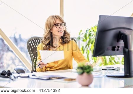 Shot Of Confident Mature Woman Sitting Behind Her Computer And Working