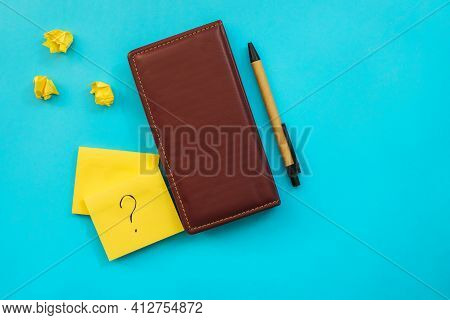 Stickers In The Form Of A Yellow Square And A Leather Notebook Lie On A Blue Background. Notebooks F