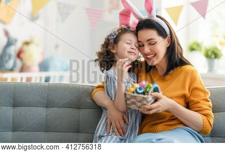 Happy holiday! Mother and her daughter with painting eggs. Family celebrating Easter. Cute little child girl is wearing bunny ears.