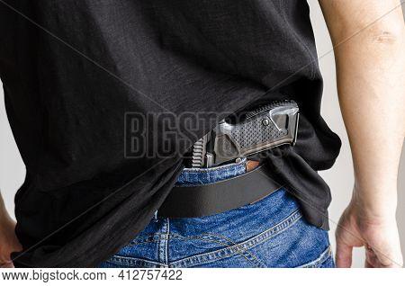 Gun. Hided Handgun Under The Denim Belt.