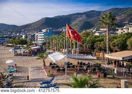 Alanya , Turkey- October 20, 2020:The flag of Turkey flutters on Kleopatra's beach  on suny day Alanya. Turkey.