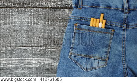 Cigarettes In The Back Pocket Of Blue Jeans. Jeans Made Of Cigarettes On Black And White Background,