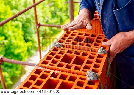 Mason, Bricklayer Worker Is Using Red Blocks To Mount A Wall Next The String Line To Be Straight.