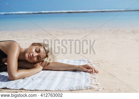 Cropped Shot Of Beautiful Blond Woman Sunbathing On Tropical Beach Near Ocean Shore. Female Tourist