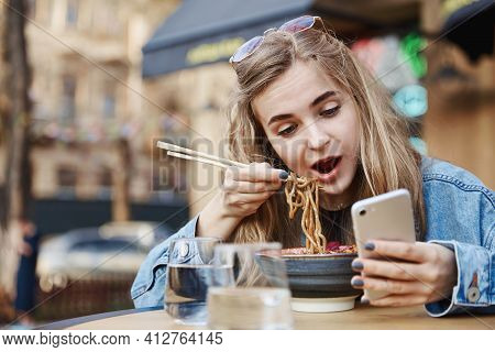 Cute Girl Eating Chinese Noodles And Looking At Phone, Holding Chopsticks And Watching Videos On Sma