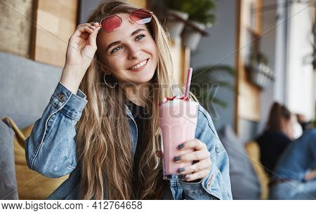 Happy Girl Take-off Sunglasses And Drinking Smoothie In Cafe Terrace, Looking Outside At Street. Blo