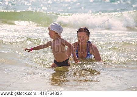 Family Swims In Sea Waves On The Beach