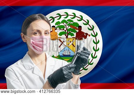 Girl Doctor Prepares Vaccination Against The Background Of The Belize Flag. Vaccination Concept Beli