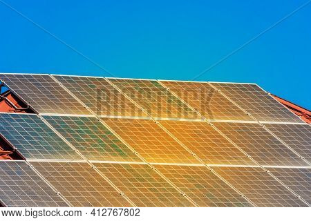 Solar Panels On The Roof Of A Building Against A Blue Sunny Sky.