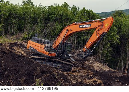 Bulgaria, Polski Trambesh, May 20th, 2020: One Chain Excavator Digging The Terrain On A Slope And Cl