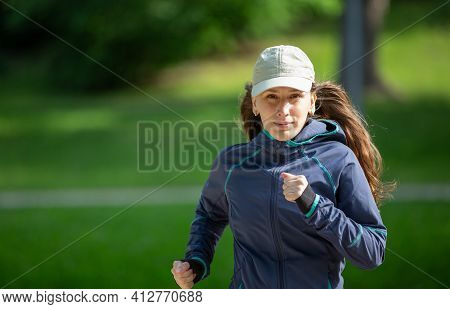 Portrait Of Woman Jogging In Park On Sunny Day