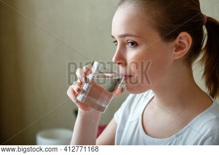 Young Woman Drinks Glass Of Pure Water In Morning After Waking Up. Happy Teen Girl Maintains Water B