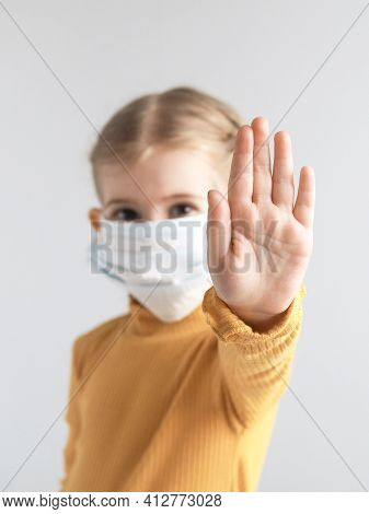 Covid-19. Coronavirus Concept. Little Girl Child Wearing Mask For Protection From Disease And Showin
