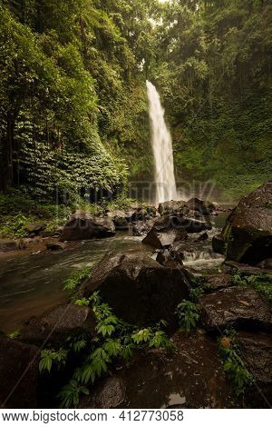 Waterfall Landscape. Beautiful Hidden Waterfall In Tropical Rainforest. Foreground With Big Stones.